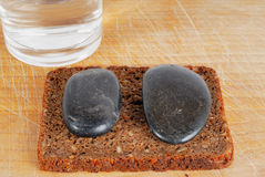 Rough but slimming diet. A photo of a loaf of corny bread served with two stones and a glass of  water Stock Photo