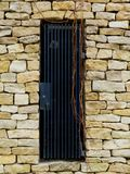 Rough split faced white textured stone wall detail with steel grille. Yellow and white colored rough split faced stone textured wall detail with deep blue steel stock photography
