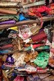 Rough stacking of clothing on shelf Stock Photos