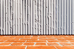 Rough Steel Siding Over a Brick Floor. Rough galvanized steel siding with a brick walkway in the front Royalty Free Stock Photo
