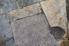 Rough stone tile floor with cracks and small stones abstract background texture.  Royalty Free Stock Photo