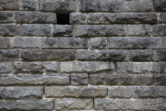 Rough stone wall with small black hole. Rough granite stone brick wall background with small window hole Royalty Free Stock Images