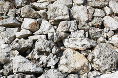 Rough stones dry wall background in sunlight Stock Photos