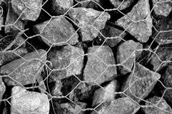 Rough stones and Metal mesh Stock Photo