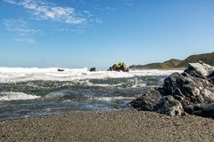 Black Pebble Sand At New Zealand Beach. Rough surf at rugged New Zealand shoreline in lower north island Stock Photos