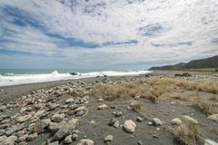 Black Sand And Rocks At New Zealand Beach. Rough surf at rugged New Zealand shoreline in lower north island Stock Photography