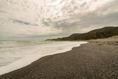 NZ Black Sand Beach. Rough surf at rugged New Zealand shoreline in lower north island stock images