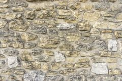 Rough surface of random pattern rastic of brown and light yellow color natural free form sand stone cladding on the concrete wall stock images