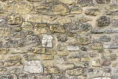 Rough surface of random pattern rastic of brown and light yellow color natural free form sand stone cladding on the concrete wall royalty free stock image