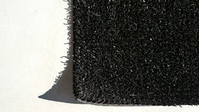 The rough texture black rug on the white epoxy floor Royalty Free Stock Images