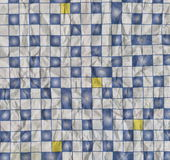 Rough texture of crumpled paper printed with abstract geometric ornament in the form of a blue and white square tiles. Stock Image