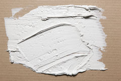 Rough texture of smeared white stucco on cardboard. White stucco smeared on grey cardboard with spatula, rough texture, closeup. Building, construction, material Stock Photos