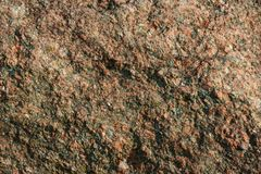 Rough and textured pink granite background. Close up of a pink granite boulder with a rough texture Stock Images