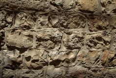 Chiaroscuro Stone Wall Texture. Rough textured yellow stone wall (from the famous 'Jerusalem Stone'), sunlit bu high-noon sun. Shot at the old city of Jerusalem Royalty Free Stock Image
