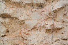 A rough untreated surface is a natural stone surface. The texture of the natural rock is the background. Granite or cracked marble.  Stock Images