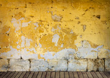 Rough wall with peeling yellow paint Stock Photos