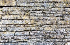 Rough weathered stone wall as background texture. Rough weathered stone wall as creative background texture. Natural stones masonry with uneven seams royalty free stock images