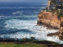 Rough Seas on Sandstone Cliffs. Rough white foamy tidal Pacific Ocean waves crashing on the base of weathered and eroded sandstone cliffs, Dover Heights, Sydney Royalty Free Stock Photo