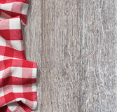 Rough wood kitchen table with red picnic cloth Stock Images