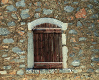 Rough wooden shutters in old stone wall Royalty Free Stock Photos
