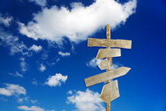 Rough wooden signposts. Directional unfinished wood signs over a blue sky and puffy white clouds Stock Photography