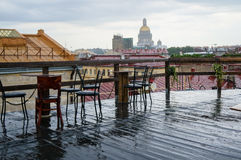 Rough wooden table, on the background of St. Petersburg, in a rooftop cafe on a rainy day. Summer 2016. Royalty Free Stock Photos