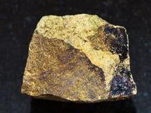 Rough yellow Chalcopyrite stone on dark Stock Photo