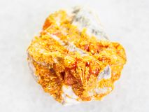 Rough yellow Orpiment crystals on white dolomite. Macro shooting of natural mineral rock specimen - rough yellow Orpiment crystals on white dolomite stone on Stock Photo