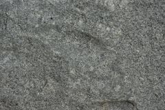 Roughly chiseled panel of igneous rock. Roughly chiseled panel of gray and white igneous rock with sections of rock missing stock photo