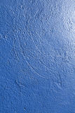 Roughly plastered wall painted in blue color Stock Photos