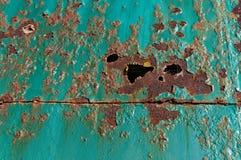 Rouille et trous de Brown sur une porte en métal de sarcelle d'hiver photographie stock libre de droits