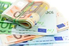 Roulé avec d'euro notes en caoutchouc sur le fond blanc Photos stock