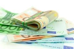 Roulé avec d'euro notes en caoutchouc sur le fond blanc Photos libres de droits