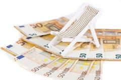 Roulé vers le haut du paquet d'euro billets de banque sur la chaise de plate-forme miniature Image stock