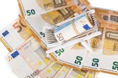 Roulé vers le haut du paquet d'euro billets de banque sur la chaise de plate-forme miniature Photos stock