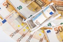 Roulé vers le haut du paquet d'euro billets de banque sur la chaise de plate-forme miniature Photo libre de droits