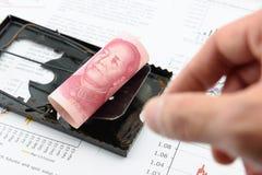 Roulé vers le haut du rouleau de facture de yuans du Chinois 100 de CNY avec le portrait/image de Mao Zedong sur un piège de rat  Photo stock