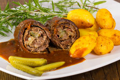Roulade with baked potatoes. Sauce and pickles Royalty Free Stock Image