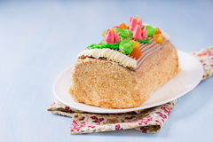 Roulade cake, decorated with colourful buttercream flowers Stock Photo