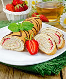 Roulade a cup of tea and strawberries on a board Royalty Free Stock Images