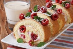 Roulade with fresh raspberries closeup and milk horizontal. Roulade with fresh raspberries and mint closeup and milk on the table. horizontal Royalty Free Stock Photography