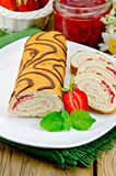 Roulade with jam and strawberries on a board Stock Images