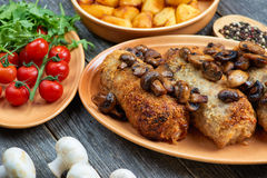 Roulade of pork with roasted mushrooms and potatoes Stock Photo