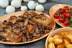 Roulade of pork with roasted mushrooms and potatoes Stock Photos