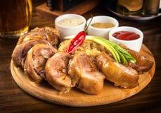 Roulade rôtie de porc avec le chou et les sauces bouillis sur le plateau en bois Photographie stock