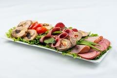 Roulades de viande avec du jambon, le fromage et des verts sur le fond blanc Image stock