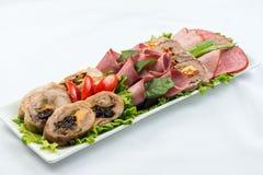 Roulades de viande avec du jambon, le fromage et des verts sur le fond blanc Photographie stock