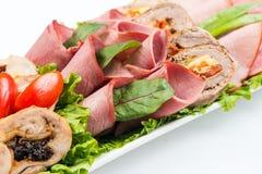 Roulades de viande avec du jambon, le fromage et des verts sur le fond blanc Images stock
