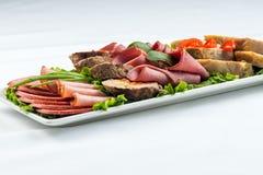 Roulades de viande avec du jambon, le fromage et des verts sur le fond blanc Photos stock