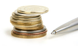 Rouleau of coins and pen Stock Images